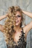 Nette junge Blondine mit langer gelockter Frisur Stockfoto