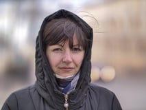Nette junge brunette Frau in einer Haube auf einer Stadtstraße, die die Kamera untersucht stockbild