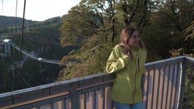Nette junge Dame, die zur Kamera freundlich auf der Front von Herbstbäumen schaut Mädchen genießen warmen Glanz des Herbstes beim stock video