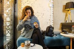 Nette junge erwachsene Frau, die Bonbons isst und Kaffee trinkt stockbilder