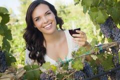 Nette junge erwachsene Frau, die ein Glas Wein im Weinberg genießt Stockfotos