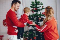 Nette junge Familienstellung nahe Weihnachtsbaum stockfotos