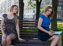 Nette junge Frau auf Bank im Parkblick am Buch ihr Zwilling Lizenzfreies Stockbild