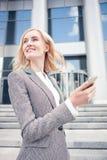 Nette junge Frau benutzt Telefon für Stockfotos