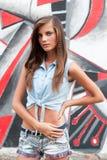 Nette junge Frau in den Jeans entsprechen nahe Backsteinmauer Lizenzfreie Stockfotografie