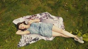 Nette junge Frau der Himmelansicht auf grünem Gras Schönes Mädchen, das auf Gras sich entspannt lizenzfreie stockfotos
