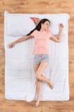 Nette junge Frau, die auf Bett liegt und schläft Stockfotografie