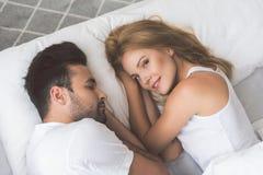 Nette junge Frau, die auf Bett nahe ihrem Ehemann liegt stockbild