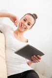 Nette junge Frau, die auf der Couch sich entspannt Stockfoto