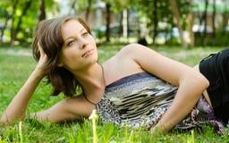 Nette junge Frau, die auf Grasfeld am Park liegt Lizenzfreie Stockfotos
