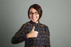 Nette junge Frau, die Daumen herauf Zeichen auf grauem Hintergrund zeigt Stockfoto