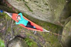 Nette junge Frau, die in der Hängematte nahe Klippe sich entspannt lizenzfreie stockbilder