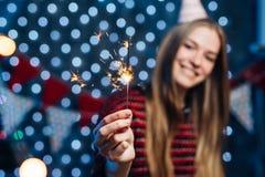 Nette junge Frau, die in der Hand Wunderkerze hält Weihnachtsneues Jahr lizenzfreie stockfotos