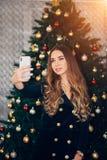 Nette junge Frau, die ein Weihnachten-selfie mit Smartphone nahe Weihnachtsbaum nimmt stockbild