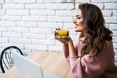 Nette junge Frau, die eine Tasse Tee bei der Anwendung ihres Laptops in ihrer Küche isst lizenzfreies stockbild