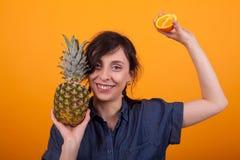 Nette junge Frau, die exotische Früchte an der Kamera im Studio über gelbem Hintergrund lächelt und zeigt stockbild