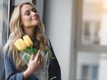 Nette junge Frau, die gelbe Tulpen hält stockfotos