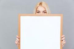 Nette junge Frau, die ihr Gesicht hinter leerem weißem Brett versteckt Lizenzfreie Stockbilder