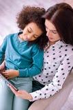 Nette junge Frau, die ihr Kind auf Knien hält lizenzfreie stockfotos