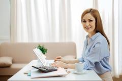 Nette junge Frau, die an ihrem Laptop arbeitet Lizenzfreies Stockfoto