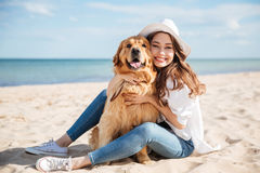 Nette junge Frau, die ihren Hund auf Strand sitzt und umarmt stockfotografie