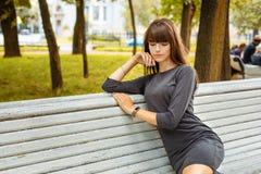 Nette junge Frau, die im Park auf einer Holzbank l?chelt stockfoto