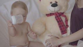 Nette junge Frau, die mit ihrem Baby sitzt, das, spielend mit der Babyflasche, die im Bett sitzt, gebotener Spielzeugbär nah ist stock video footage