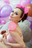 Nette junge Frau, die mit rosa Lutscher aufwirft Lizenzfreie Stockfotos