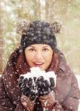 Nette junge Frau, die mit Schnee spielt Stockfoto