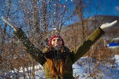 Nette junge Frau, die mit Schnee spielt Lizenzfreie Stockfotografie