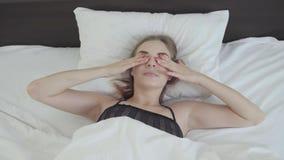 Nette junge Frau, die morgens im Bett liegt Das Mädchen wachte gerade das Ausdehnen und das Betrachten des Kameralächelns auf Fre stock video