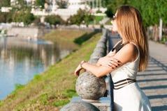 Nette junge Frau, die nahe einem Fluss stillsteht lizenzfreies stockfoto