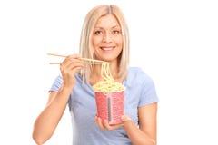 Nette junge Frau, die Nudeln isst stockfoto