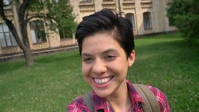 Nette junge Frau, die selfie nimmt und sich Daumen zeigt, auf Gras im Park nahe Universität lächelt und steht stock video footage