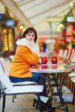 Nette junge Frau, die Weihnachtsjahreszeit in Paris genießt Stockbild