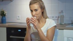 Nette junge Frau, die zu Hause Becher in der Küche hält stock footage