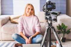 Nette junge Frau, die zu Hause blogging ist Stockbilder