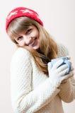 Nette junge Frau in gestrickten Handschuhen und in Kappe mit Schneeflocken eines Musters, weißes Strickjackengetränk-Getränkeglück Lizenzfreie Stockbilder