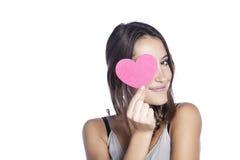Nette junge Frau hält ein Innersymbol zu ihrem Gesicht an Roter heart-shaped Schmucksachegeschenkkasten und eine rote Spule auf e Lizenzfreie Stockfotos