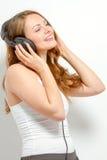 Nette junge Frau hört auf Kopfhörer Lizenzfreies Stockfoto
