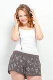 Nette junge Frau hört auf Kopfhörer Lizenzfreie Stockfotos
