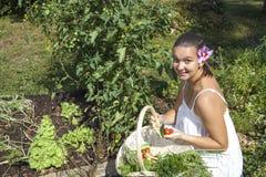 Nette junge Frau in ihrem Garten lizenzfreies stockfoto
