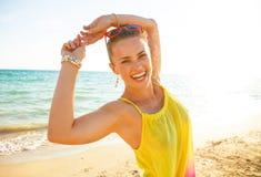Nette junge Frau im bunten Kleid auf Strand am Abend Lizenzfreie Stockbilder
