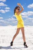 Nette junge Frau im gelben Kleid auf dem Schnee Stockbilder