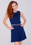 Nette junge Frau im Marineblaukleid auf Weiß Stockfotografie