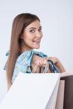 Nette junge Frau ist gehender Einkauf mit Stockbild
