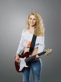 nette junge Frau mit Gitarre im Studio Lizenzfreie Stockfotos