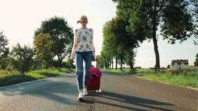 Nette junge Frau mit Koffer gehend auf Straße stock footage