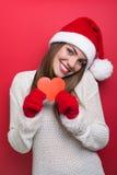 Nette junge Frau mit Sankt-Hut, der rotes Papierherz zeigt Stockbild