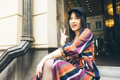 Nette junge Frau sitzt auf den Schritten einer Boutiquenvertretungszunge lizenzfreies stockfoto